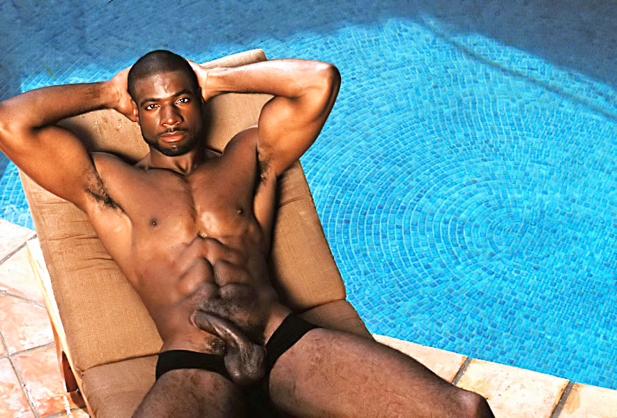 Massive black dude relaxing at the pool bench.
